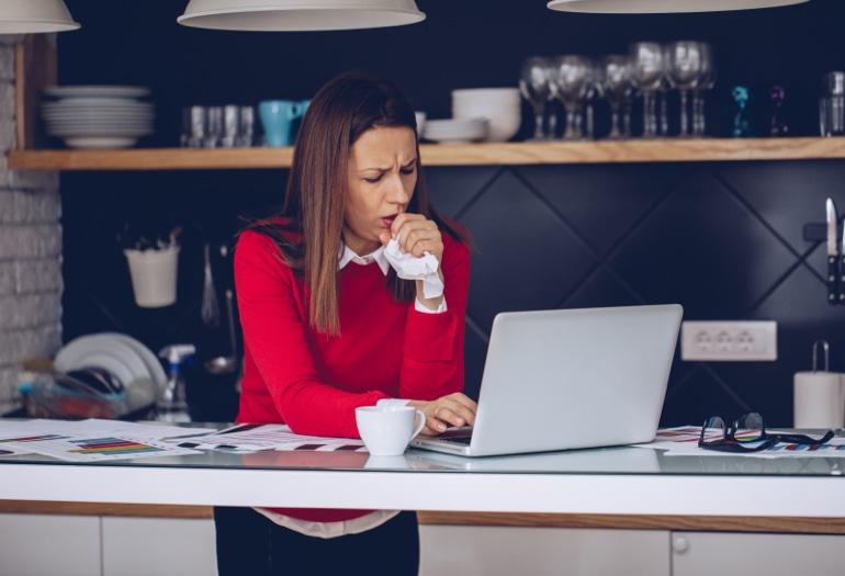 Co powoduje kaszel? Kobieta stoi w kuchni i pracuje na laptopie, kaszląc chusteczkę.