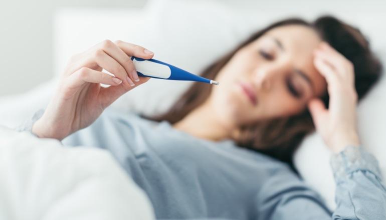 Kobieta z przeziębieniem leży w łóżku i patrzy na termometr