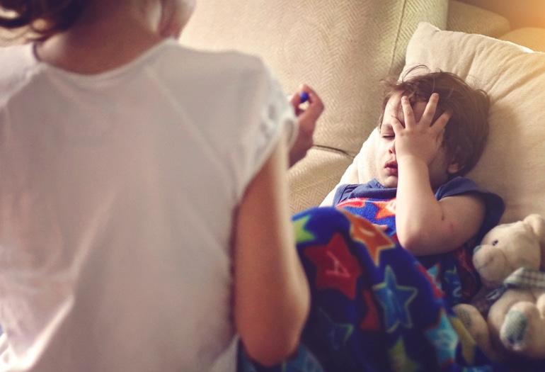Chore dziecko z mokrym kaszlem leży w kocu, trzymając się za głowę