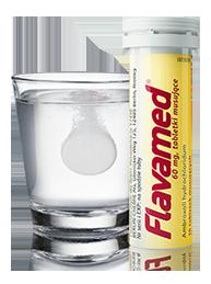 Tabletka musująca rozpuszcza się w wodzie obok opakowania Flavamed® Tabletki musujące 60 mg na kaszel mokry